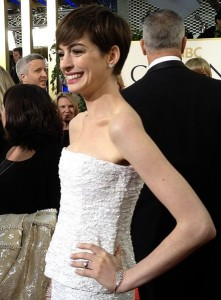 Anne Hathaway poses at the Golden Globes, wearing her favorite Kwiat jewels including diamond cluster earrings, bracelets, and of course her beautiful engagement ring. Photo taken by Jenn Deering Davis, licensed under Creative Commons.