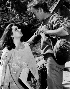 Press photo of Elizabeth Taylor and Richard Burton in the film, The Sandpiper. This work is in the public domain in that it was published in the United States between 1923 and 1977 and without a copyright notice.