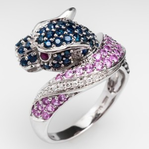 This pink and blue sapphire panther cocktail ring evokes the mystique of Nina Dyer's Cartier Panther jewels. Nina's panthers were embodied in white diamonds with blue sapphire spots and green garnet eyes. Photo ©2015 EraGem Jewelry.