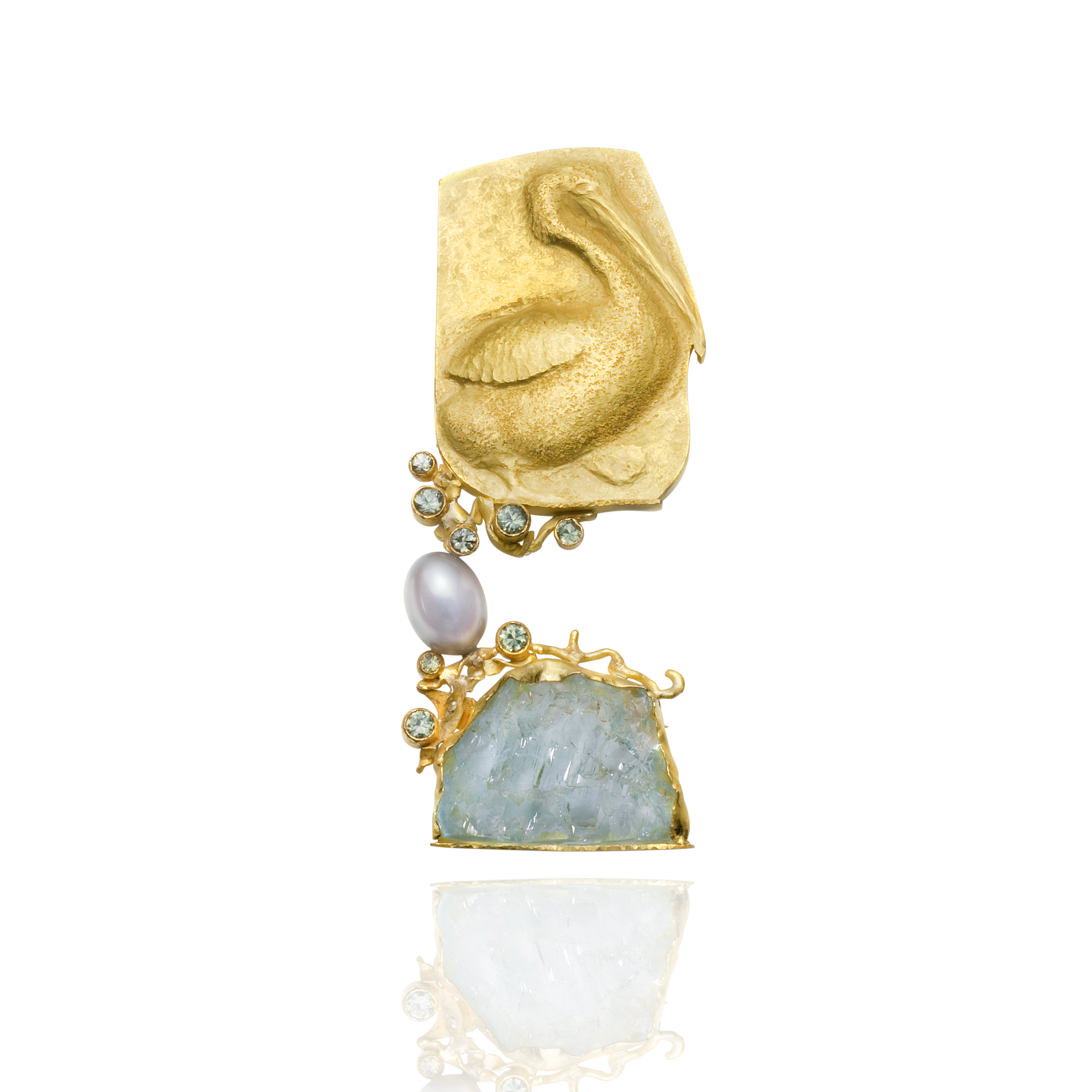"""Baby Pelican"" by Linda Kindler-Priest. Two-part brooch in 14k yellow gold, green sapphires, pearl, and aquamarine rough. Photo used with permission."