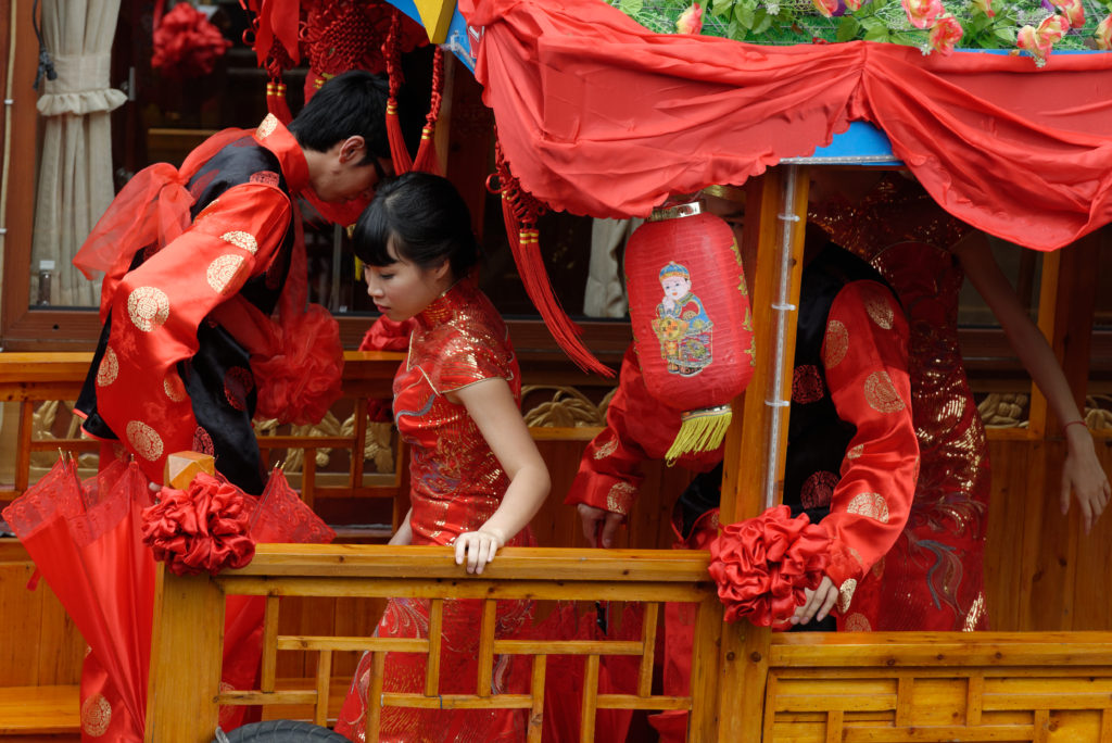 A Chinese wedding begins as the bride exits the seddan chair outside her groom's home.